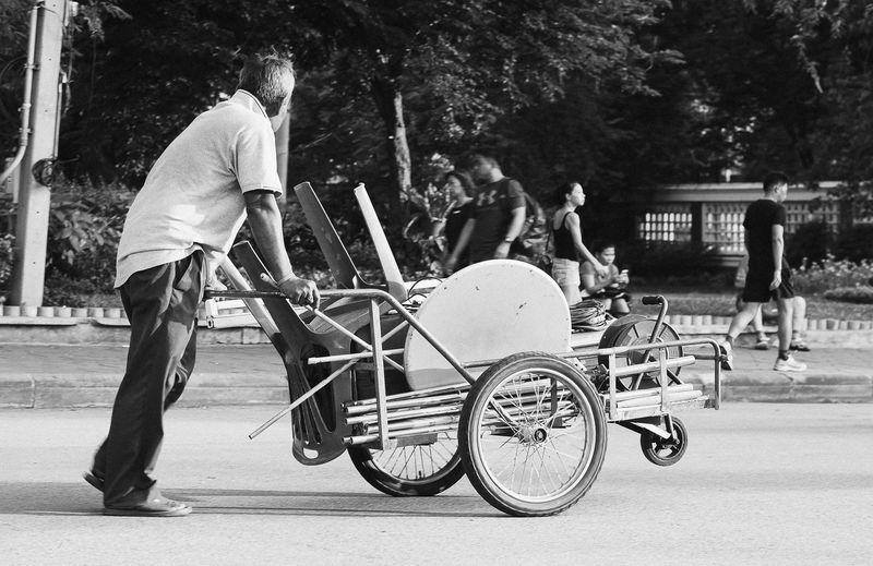 Man pushing chairs on cart