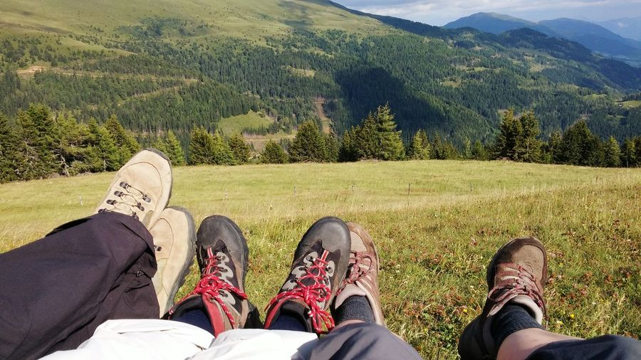 Low Section Of Friends Lying On Grassy Field Against Mountain