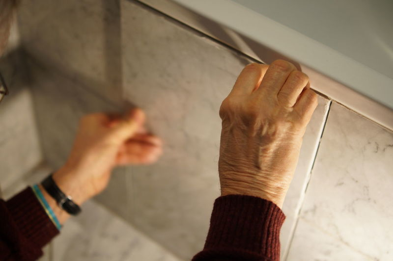 Cropped hands placing tile on wall