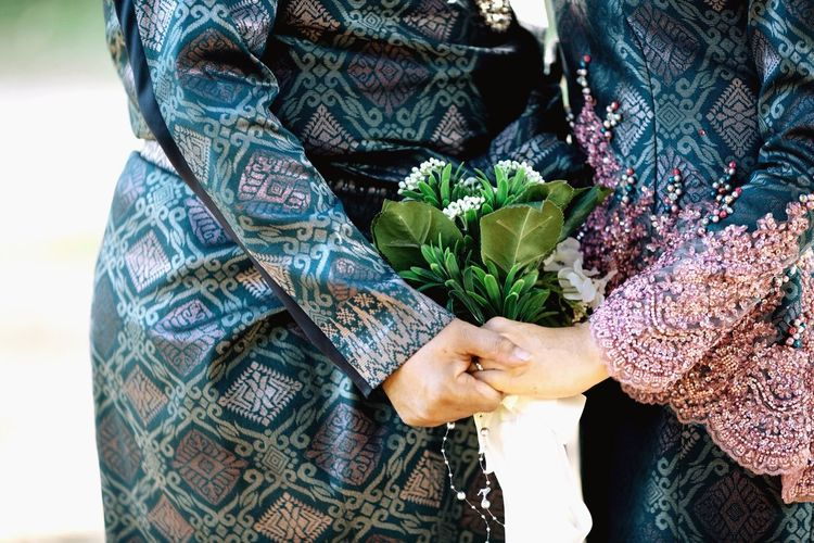 Midsection of couple holding hands and flower bouquet