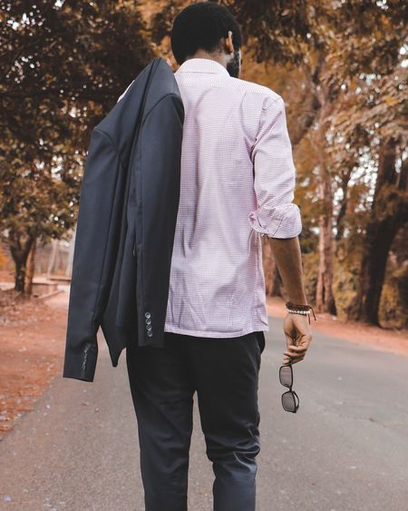 Rear View Of Man With Blazer Walking On Road