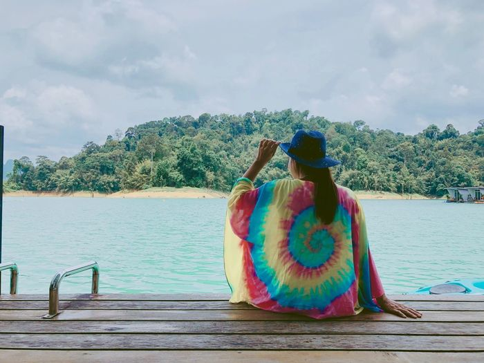 Sky Water Real People Rear View One Person Cloud - Sky Nature Lifestyles Leisure Activity Sitting Day Tree Adult Beauty In Nature Women Lake Clothing Plant Outdoors Human Arm Arms Raised Looking At View