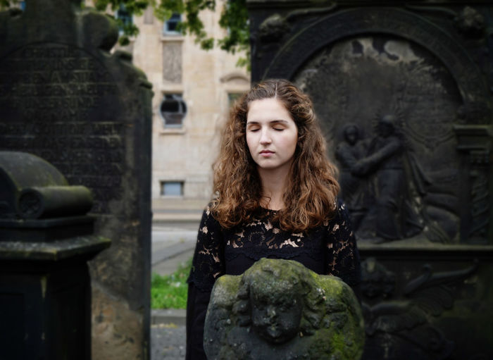 Young Woman Standing By Sculpture At Graveyard