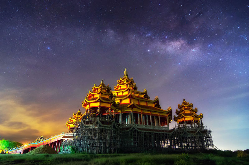 Low angle view of temple against star field at night