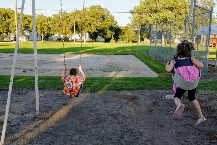 Siblings playing at swing on playground
