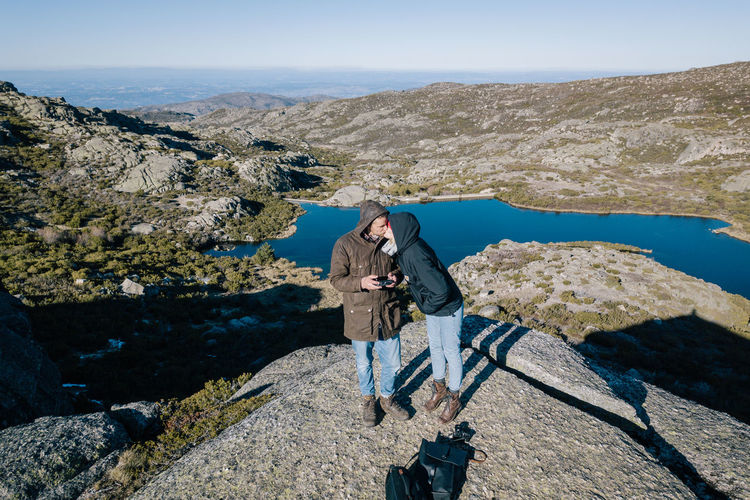 Couple Kissing While Standing On Mountain Against Clear Sky