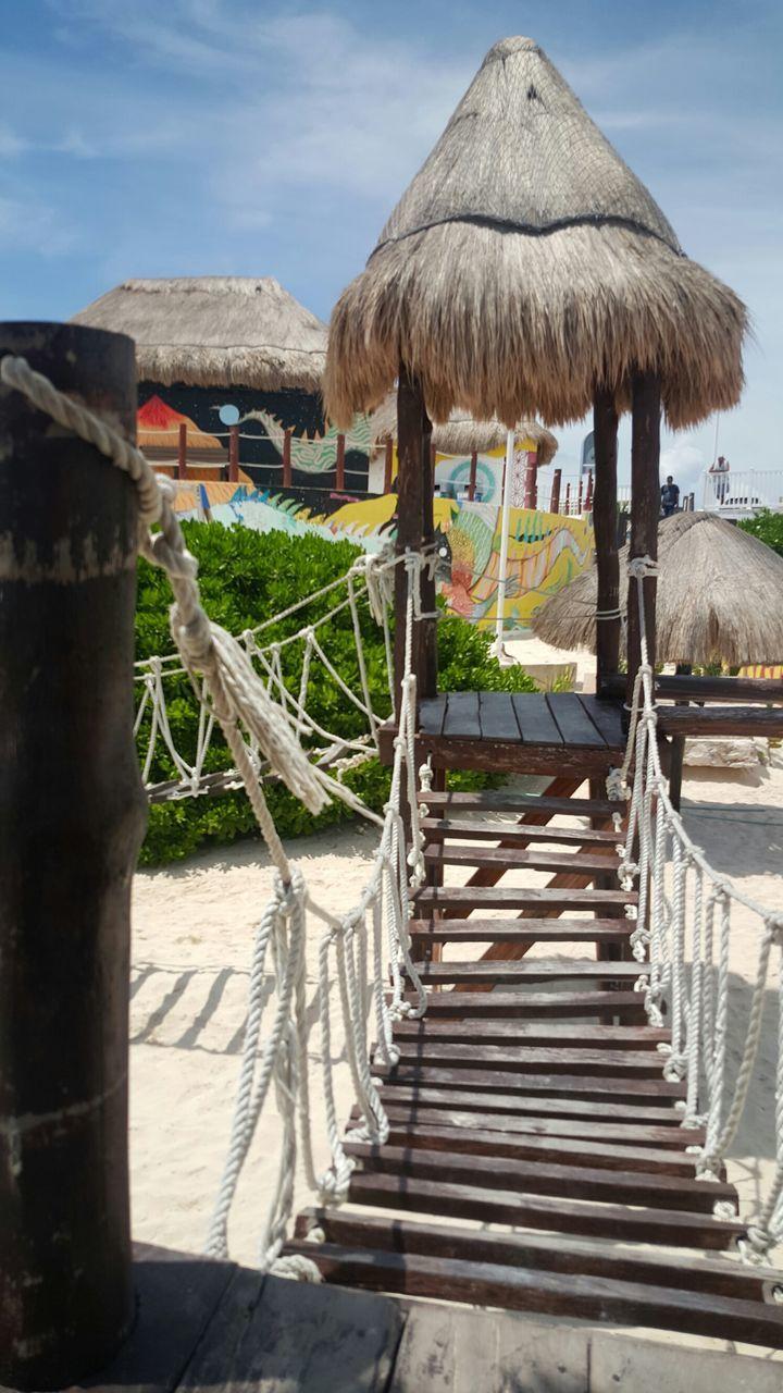 Footbridge By Gazebo On Beach Against Sky