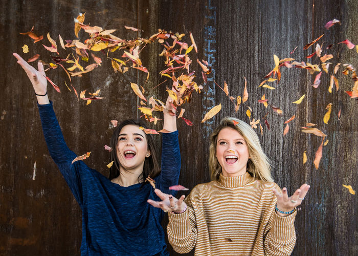 Sisters throwing fall leaves Arms Raised Autumn Bonding Cheerful Friendship Fun Happiness Human Arm Leaf Only Women People Portrait Smiling Togetherness Two People Young Women