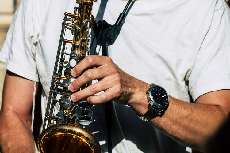 Midsection of man playing saxophone
