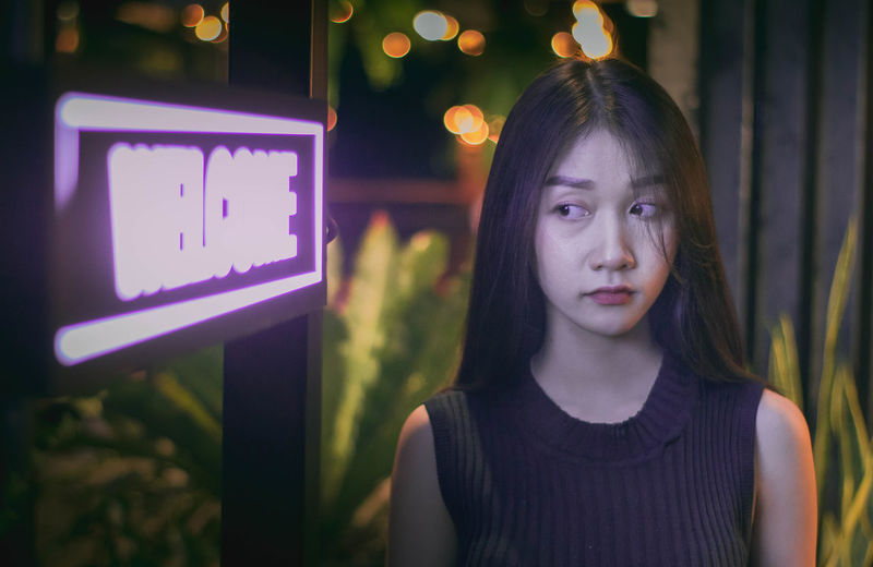 Woman looking at illuminated welcome sign
