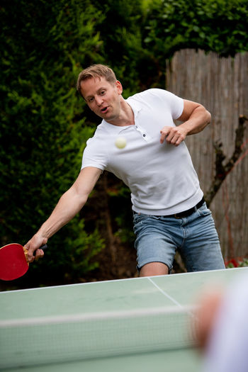 Man playing table tennis outdoors
