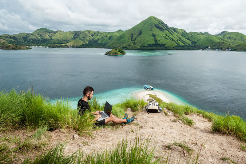 A man with a laptop working remotely on the tropical island