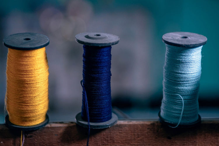 Spools of blue and yellow threads for sewing purposes. Needlework Textile Industry Art And Craft Blue Close-up Cloth Clothing Indoors  Leisure Activity Needle Pattern Selective Focus Sewing Item Side By Side Spool Textile Thread Threads Tool Variation Wood - Material Wool Yarn