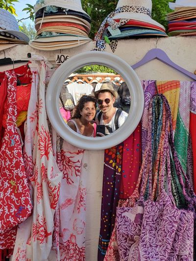 Reflection of couple on mirror at market stall