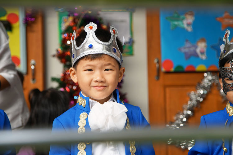 Portrait of smiling boy wearing crown while standing in party