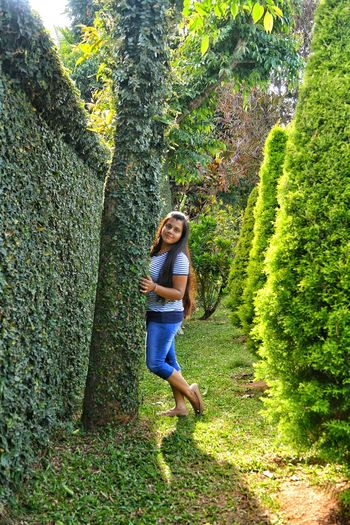 Full Length Portrait Of Young Woman Standing By Tree