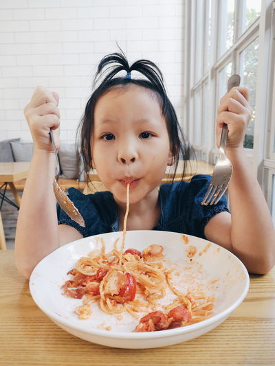 Portrait of girl eating spaghetti while sitting in restaurant