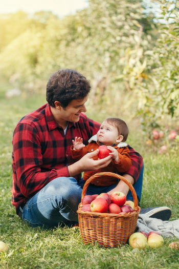 Father showing apple to son at forest