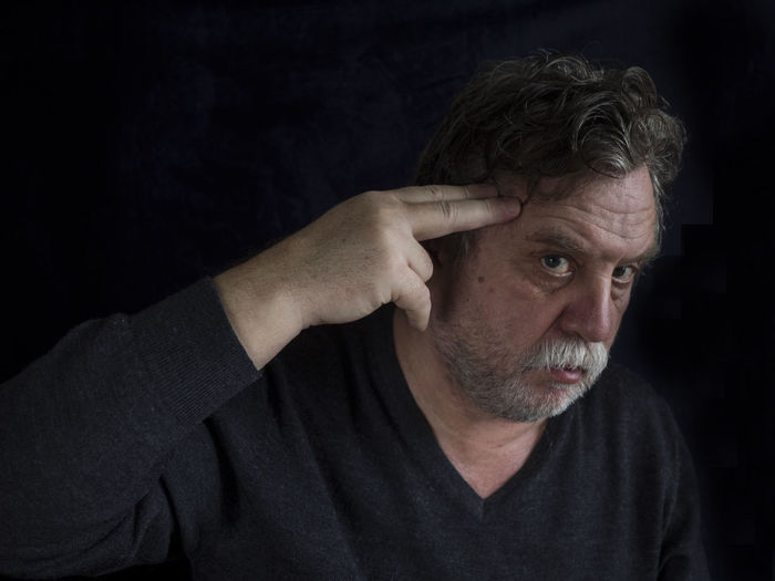 Portrait of mature man shooting himself against black background
