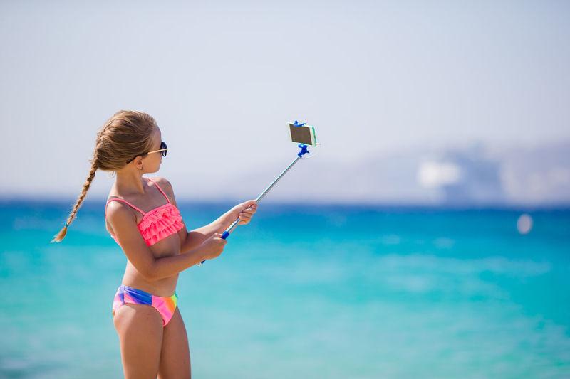 Full length of woman holding umbrella on beach