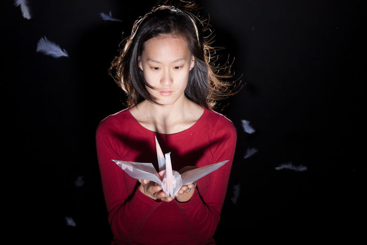 Young woman holding origami standing against black background