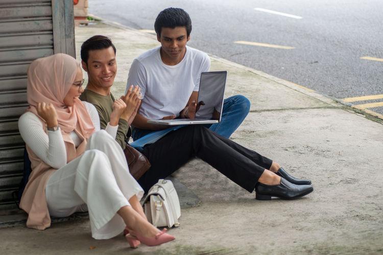 Young couple sitting on sidewalk