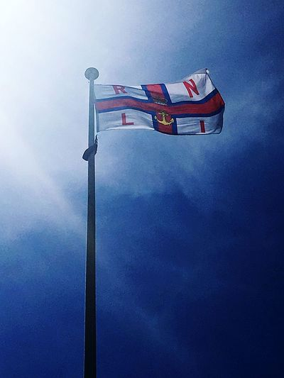 Flag Low Angle View Blue Sky RNLI Lifeboat TheLizard Savinglives Charity Proud Cornwall Day Outdoors Brand Eyeemphotography Flying High British Coast Sea Volenteer