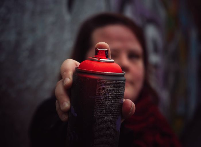 Close-up of woman holding  spray can against blurred background