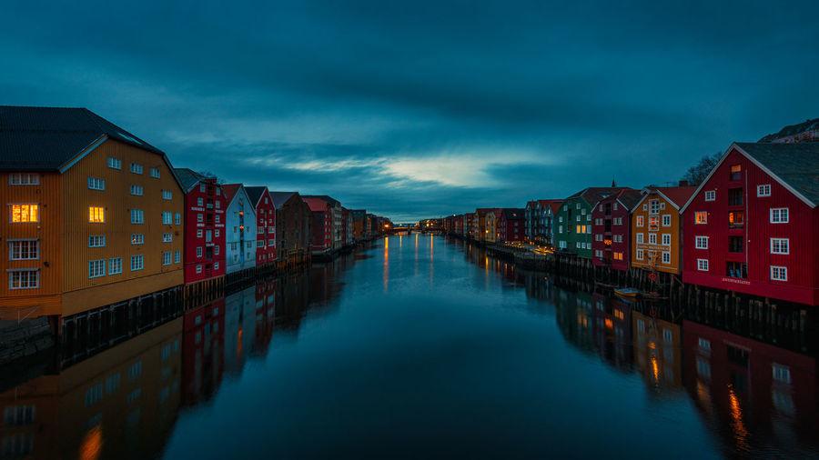 Canal amidst houses against sky at dusk