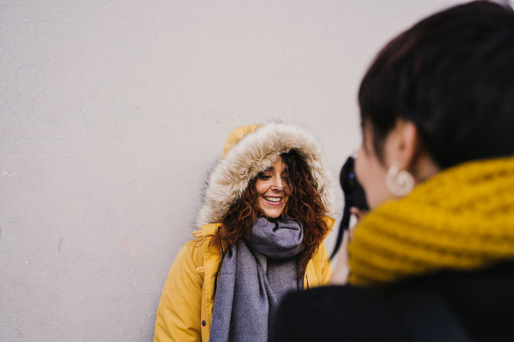 Woman photographing smiling friend against wall