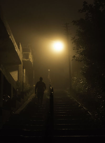 Rear view of man on footpath at night