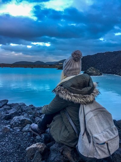 Rear view of woman sitting on rocks at blue lagoon