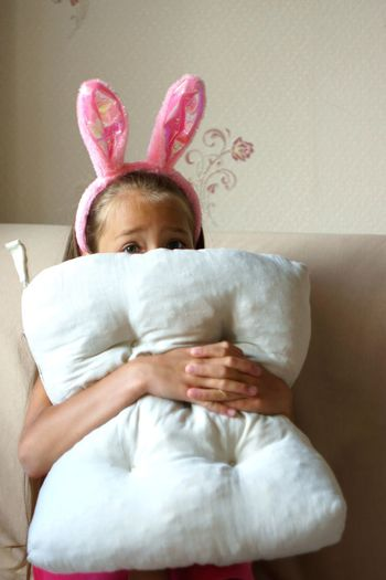 Portrait Of Girl Covering Face With Cushion At Home