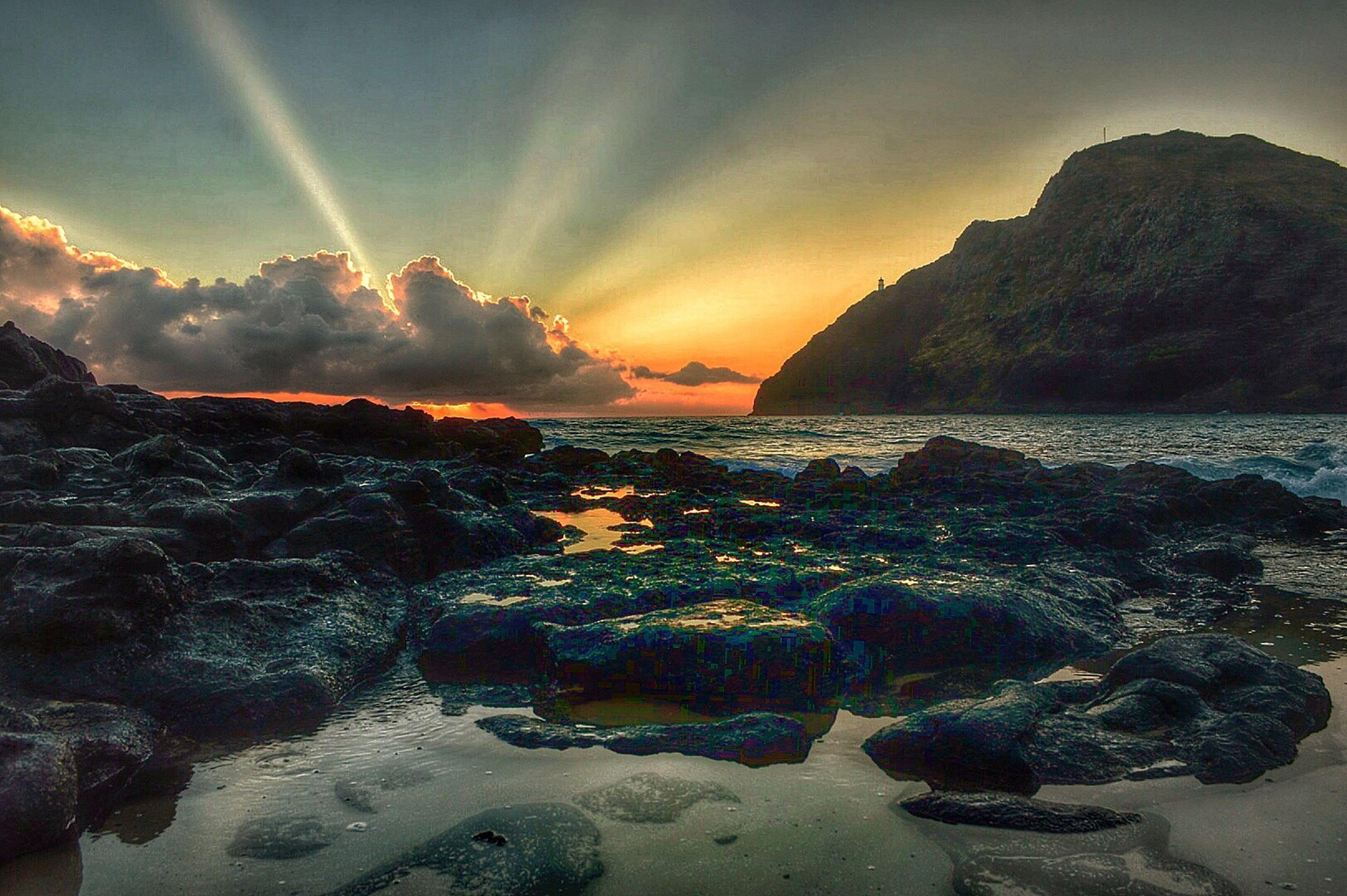 water, scenics, beauty in nature, sea, tranquil scene, sky, rock - object, sunset, tranquility, rock formation, nature, beach, mountain, idyllic, cloud - sky, shore, sun, sunbeam, sunlight, rock