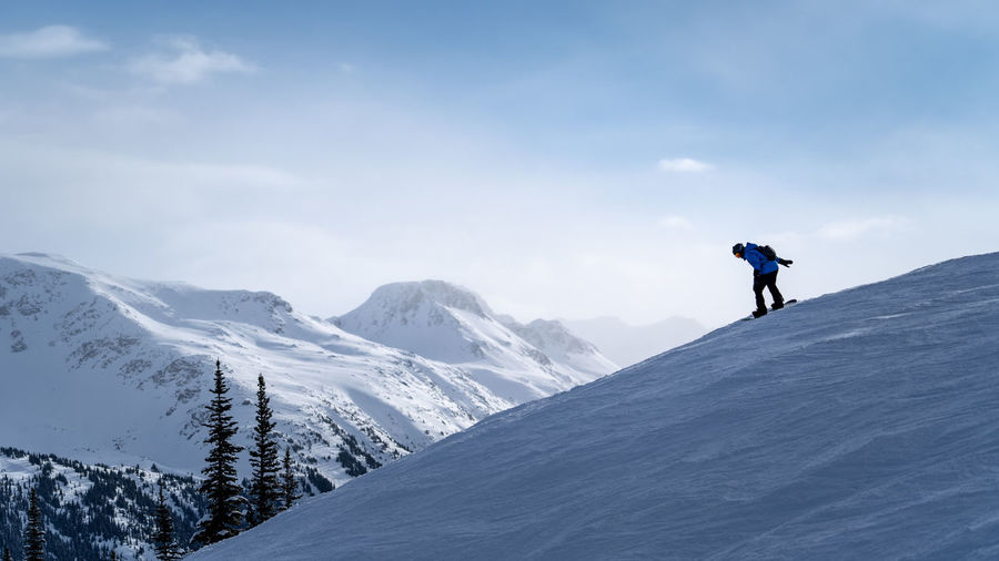 Man snowboarding on snowcapped mountain against sky