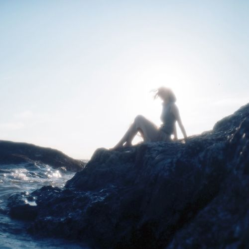 Side View Of A Silhouette Woman Sitting On Beach