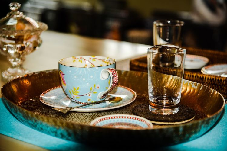 Tea Cup By Glass In Tray On Table