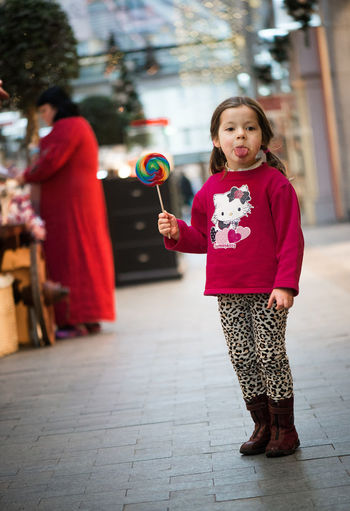 Portrait of girl eating lollipop while standing on footpath in city