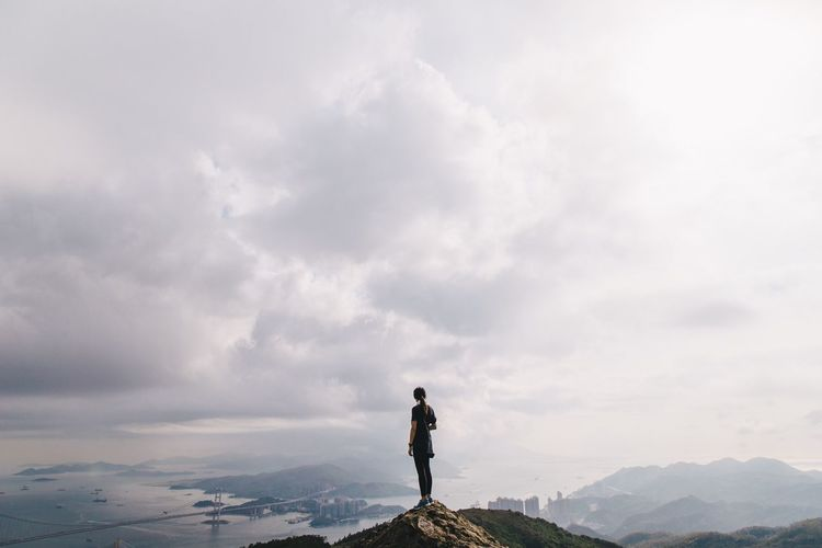 Woman Standing On Rock Against Clouds