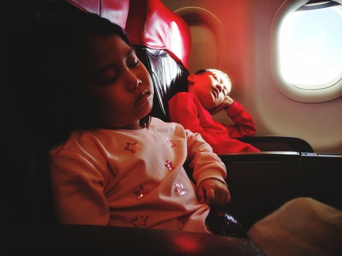 Children Sleeping While Sitting On Vehicle Seats In Airplane