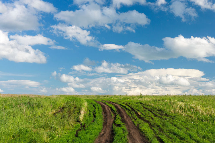 Country Road Beauty In Nature Cloud - Sky Countryside Day Environment Field Grass Green Color Horizon Horizon Over Land Land Landscape No People Outdoors Rural Scene Scenics - Nature Sky Track Tracks Tranquil Scene Tranquility