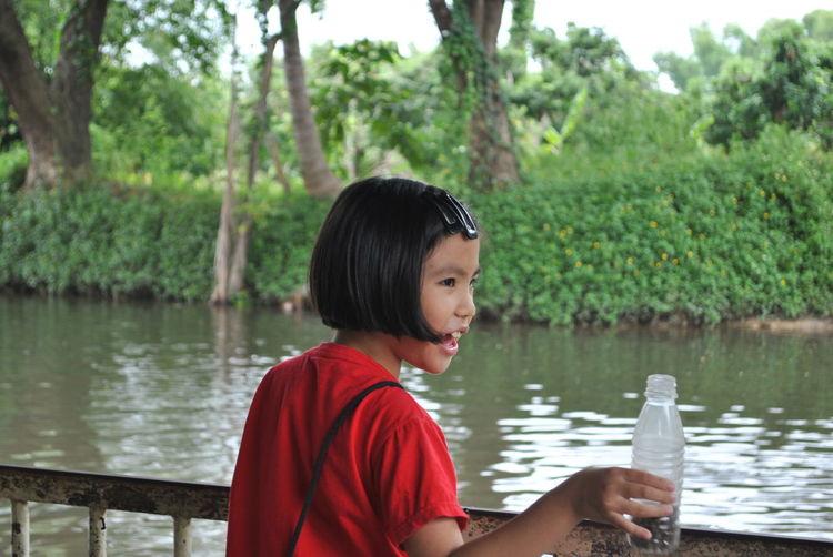 Girl holding bottle while standing against lake