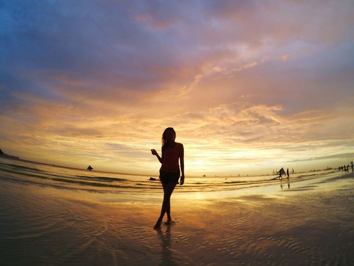 Silhouette woman standing on wet shore at beach against cloudy sky during sunset