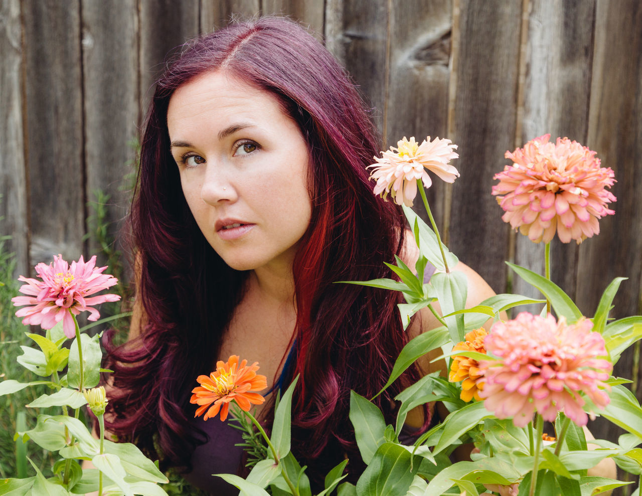 Beautiful Redhead Woman Amidst Pot Marigold Flowers Against Fence
