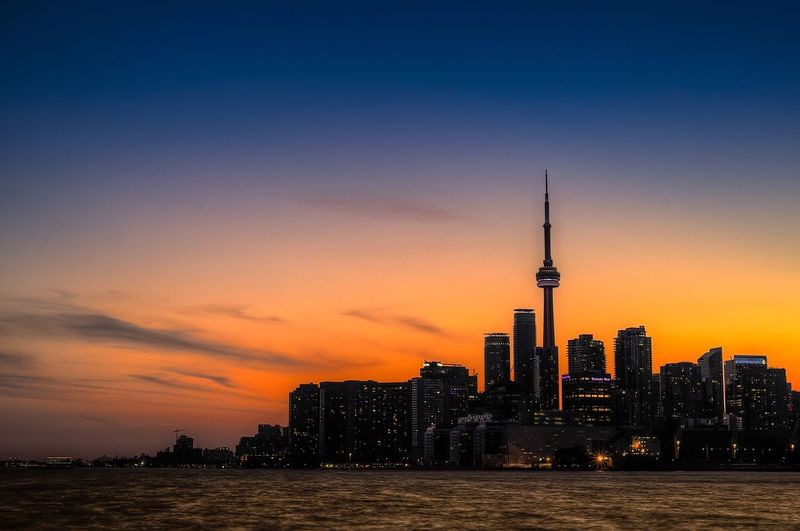 River against cn tower amidst buildings in city at sunset