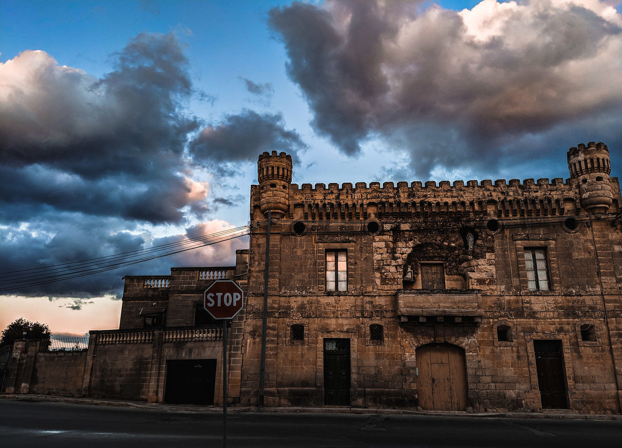 LOW ANGLE VIEW OF OLD BUILDING IN CITY AGAINST CLOUDY SKY