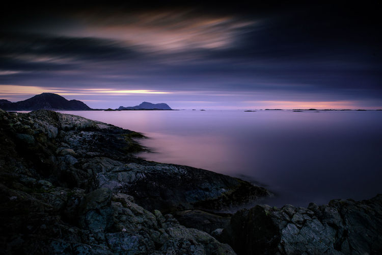 Scenic view of sea and mountains against sky at sunset