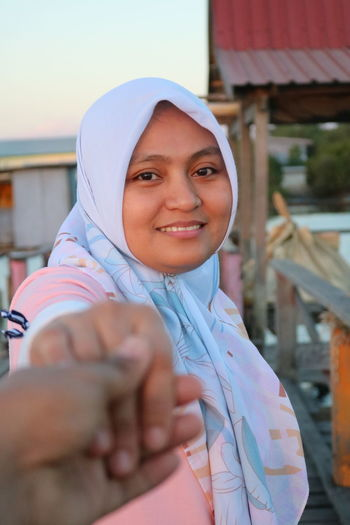 Portrait of smiling woman wearing hijab standing outdoors at sunset