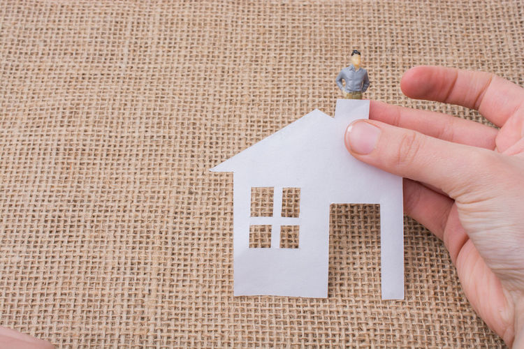 Cropped Hand Holding Paper Model Home With Male Figurine At Table