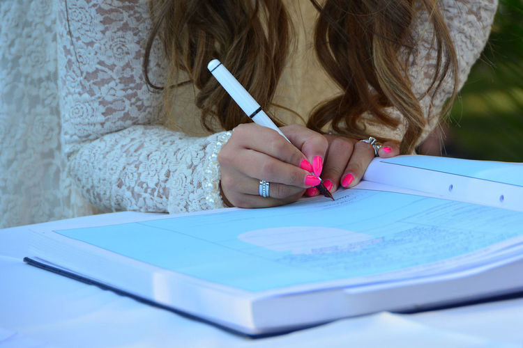 Midsection of bride writing in book on table